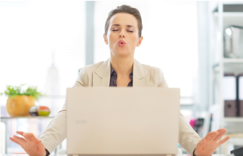 Managing stress and building resilience from the Welbee learning centre. Accept your stressors - picture of a woman in front of laptop  breathing and meditating.
