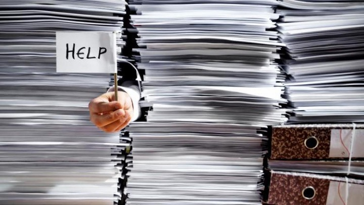 The major causes of workplace stress and poor wellbeing from the Welbee learning centre. Picture of piles of work to represent workload as one part of the Demands management standard.