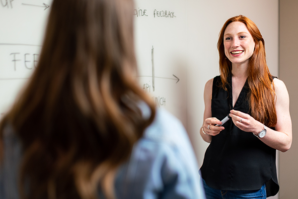 Young teacher standing next to a board, smiling and speaking to a student.